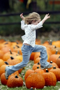 girl leaping pumpkins
